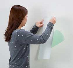 青い離けい紙をゆっくりはがし、壁面に貼り合わせる。上からスキージやローラーで十分にエア抜きをする。)